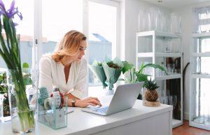 Female florist using laptop in flower shop